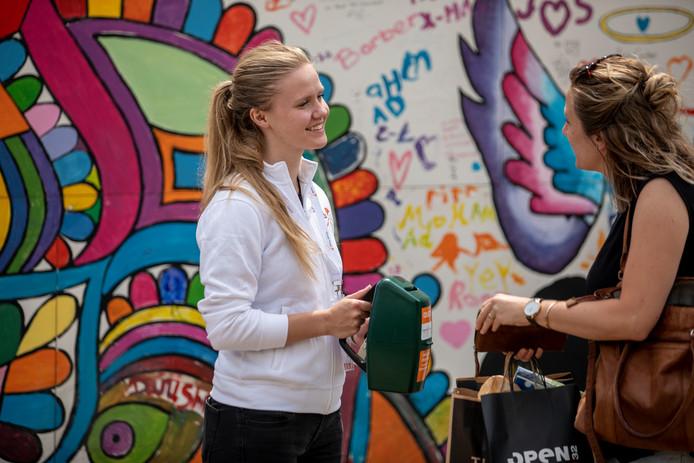 Een collectant van het Oranje Fonds krijgt geld op straat.
