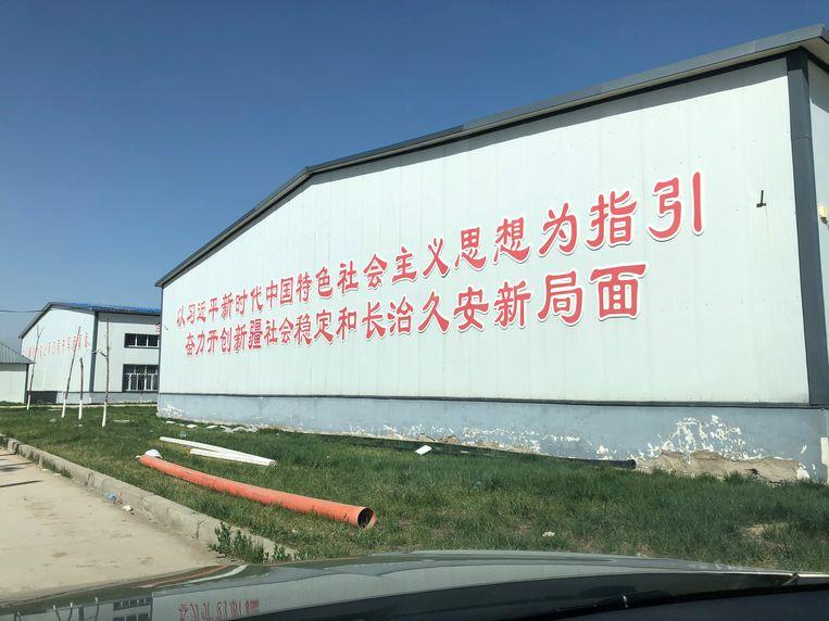 De slogan op deze fabrieksloods roept op om 'met het gedachtengoed van Xi Jinping als gids' te streven naar 'sociale stabiliteit en duurzame vrede'. Beeld Leen Vervaeke