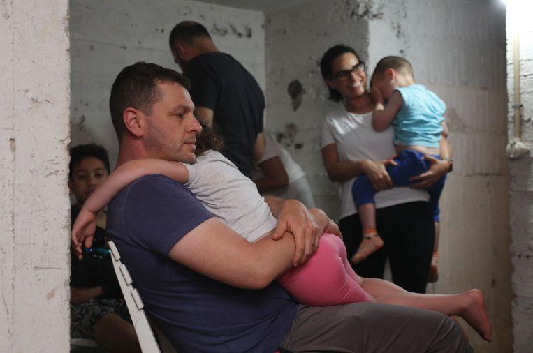 Inwoners van Tel Aviv zoeken donderdag bescherming in een schuilkelder. Volgens het Israëlische leger komen de raketten niet alleen uit de Gazastrook, maar ook uit Libanon.  Beeld AFP
