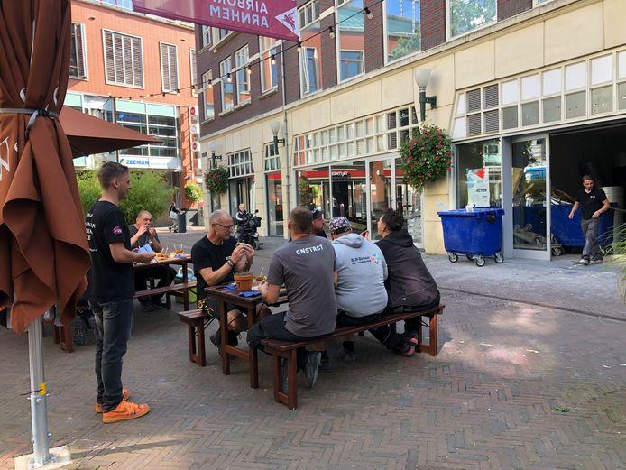 Een medewerker van WAAR SmaakLokaal Arnhem serveert de bouwploeg van de nieuwe vestiging van Action op het Brouwersplein broodjes kroket. Op de achtergrond rechts de toekomstige Action. Pal daarvoor doorlopend tot aan de hoek van de Walstraat de toekomstige winkel van Intertoys.