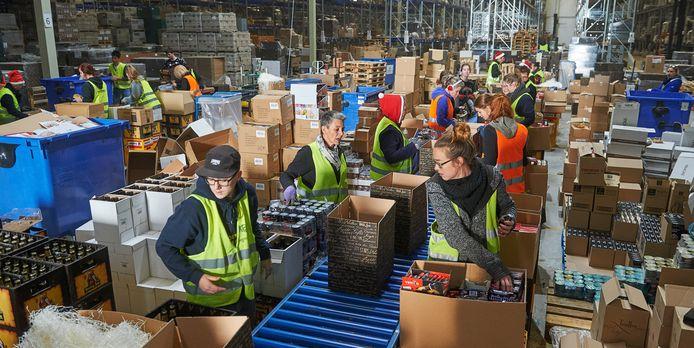 In het magazijn van Kerstpakketten.nl in Uden maken zo'n honderd medewerkers overuren om alle 250.000 kerstpakketten op tijd ingepakt en verstuurd te krijgen.