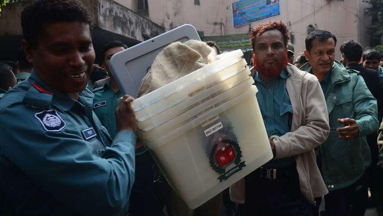 Agenten brengen stembussen naar de bureaus. Beeld AFP