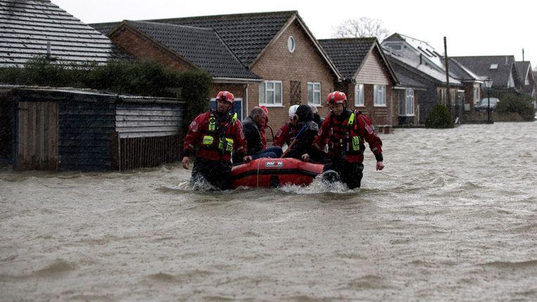 Reddingswerkers helpen evacués in Walton-on-Thames.<br /><br />De Engelse overheid waarschuwt voor ernstig overstromingsgevaar in 14 plaatsen langs de de rivier de Theems. Duizenden huishoudens moeten zich daar op voorbereiden. Sinds december zijn al zo'n 8000 woningen getroffen door het hoge water.<br /><br />Ondanks alle maatregelen is vanmiddag het dorp Datchet ook ondergelopen.<br /><br />Na twee maanden van recordneerslag voorspellen meteorologen nog zeker tot en met donderdag iedere dag regen. Vooral de graafschappen Berkshire en Surrey zullen vermoedelijk met wateroverlast te maken krijgen. <br /><br />De Britten worstelen met het natste weer sinds 1766. Het water in de rivier stond in tientallen jaren niet zo hoog en stijgt nog steeds. Beeld getty