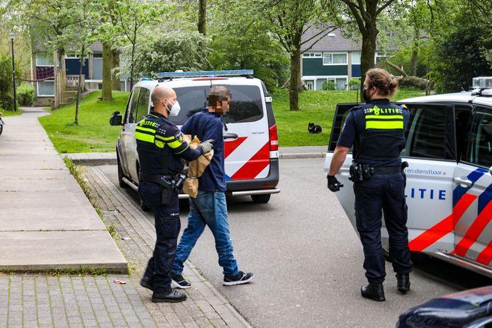 Een tweede mannelijke verdachte werd met papieren zakken om handen en armen afgevoerd: zo werd mogelijk bewijsmateriaal beschermd.