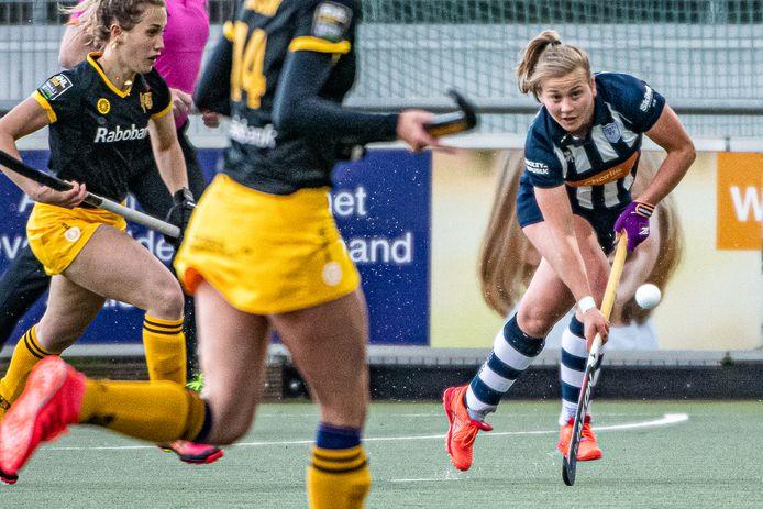 Margot van Hecking Colenbrander van HDM speert langs twee Bossche speelsters.
