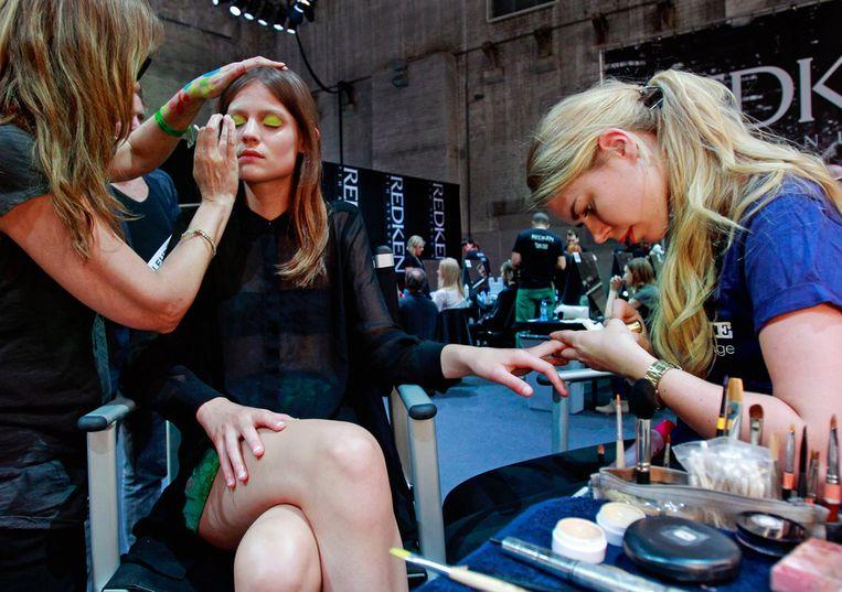 Een model wordt opgemaakt voor de show van Marga Weimans bij de zeventiende editie van de Amsterdam Fashion Week in de Westergasfabriek. Beeld null