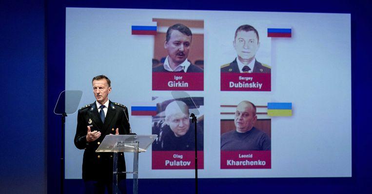 Wilbert Paulissen van het JIT met de vier verdachten op de achtergrond.