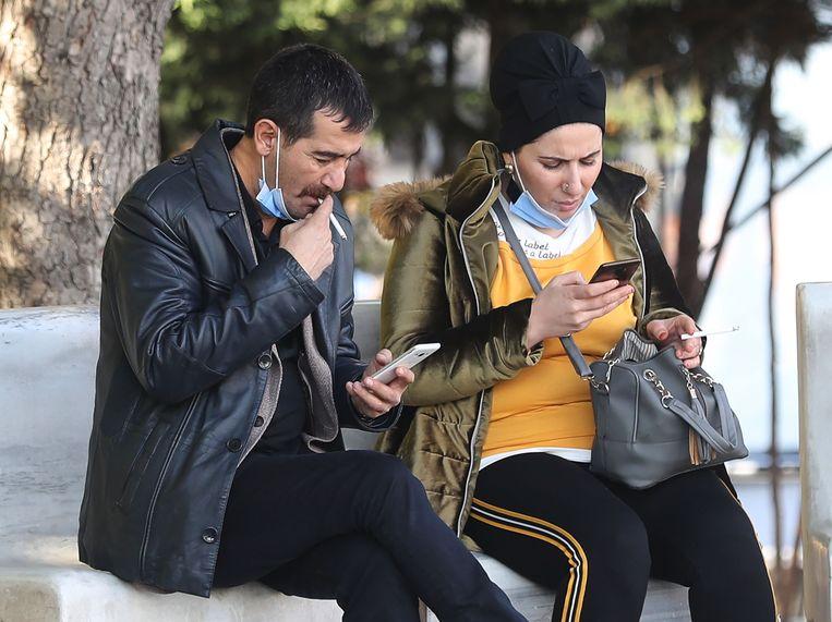 Rokende man en vrouw op straat in Ankara. Beeld AFP