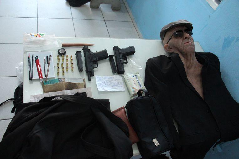 Met dit masker en nog wat roversattributen waagde een bankemployé een overval op zijn eigen bank. De politie in het Braziliaanse Santa Catarina heeft na zijn arrestatie alles uitgestald op een tafel. De wapens zijn van plastic. Beeld EPA