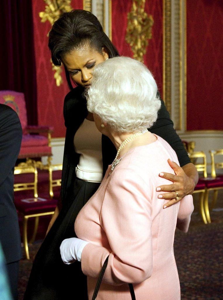 De voor veel Britten verbijsterende beelden van fysiek contact tussen Michelle Obama en koningin Elizabeth II, leidden in de Britse en Amerikaanse pers tot ernstige beschouwingen over de vraag wie als eerste overging tot het aanraken van de ander. Foto's EPA Beeld