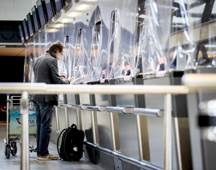Reizigers bij de incheckbalie van Transavia op Schiphol.