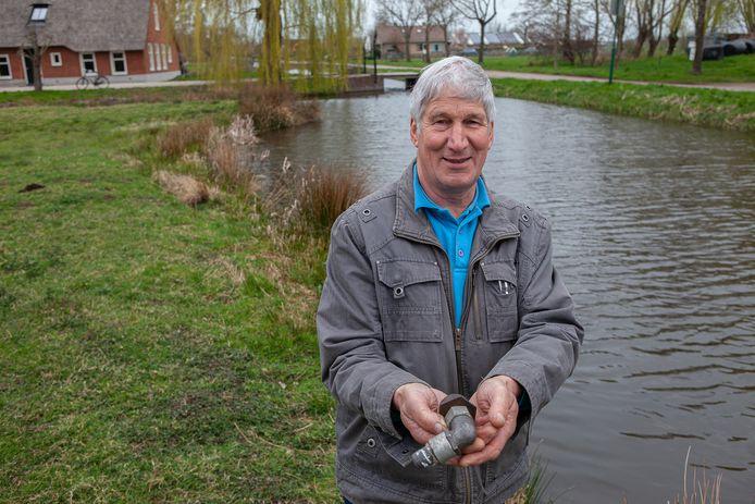 Willem van der Linden in het weiland van de boerderij van Van den Ancker waar de bommenwerper neerstortte. In zijn handen een brokstuk van het vliegtuig dat onderdeel is van de brandstoftoevoer.