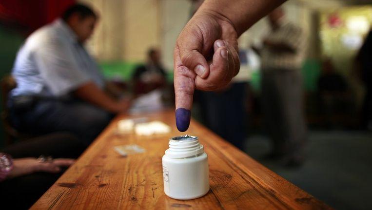 Een Egyptische man doopt zijn vinger in de inkt nadat hij gestemd heeft. Beeld reuters