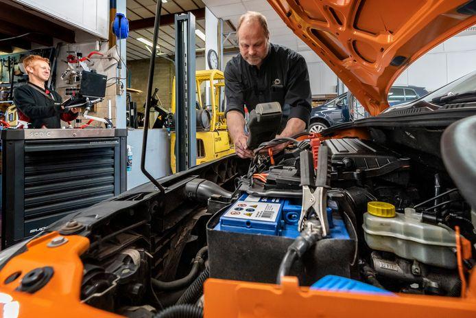 Erik Vorstenbosch, eigenaar van de gelijknamige autogarage in Schijndel, controleert de accu van een auto. Links Erwin Papen.