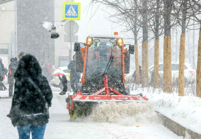 A communal vehicle cleans a sidewalk during a heavy snowfall in Moscow on January 26, 2019. - In Europe's largest city - with an official population of 12 million but likely home to several millions more - some 60,000 people and 14,000 vehicles are employed by the roads department to clear the snow. (Photo by Mladen ANTONOV / AFP)