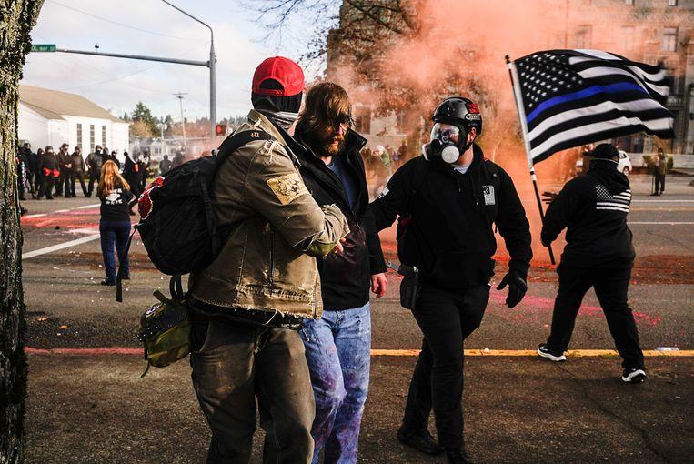 Demonstranten helpen een Trump-supporter die gewond raakte tijdens de protesten in Olympia (Washington).  Beeld Getty Images