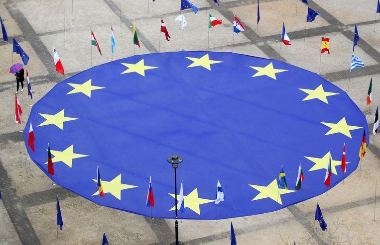 Een grote Europese vlag op het Schumanplein in Brussel, met de vlaggen van alle lidstaten.  Beeld Reuters