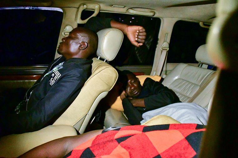 Presidentskandidaat Robert Kyagulanyi slaapt op de achterbank van zijn auto bij een benzinestation in Migera, Oeganda. De oppositieleider en zanger, ook bekend onder zijn artiestennaam Bobi Wine, is in de aanloop naar de Oegandese verkiezingen in januari al meerdere keren opgepakt. Beeld REUTERS