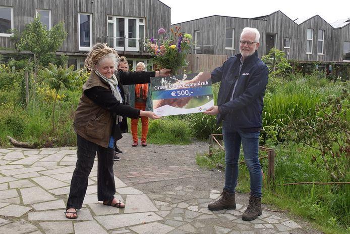 Leidi Haaijer, bewoner en mede-oprichter van Bewust Wonen & Werken Boschveld, ontvangt de prijs van Peter Ketelaars (rechts) van waterschap Aa en Maas.
