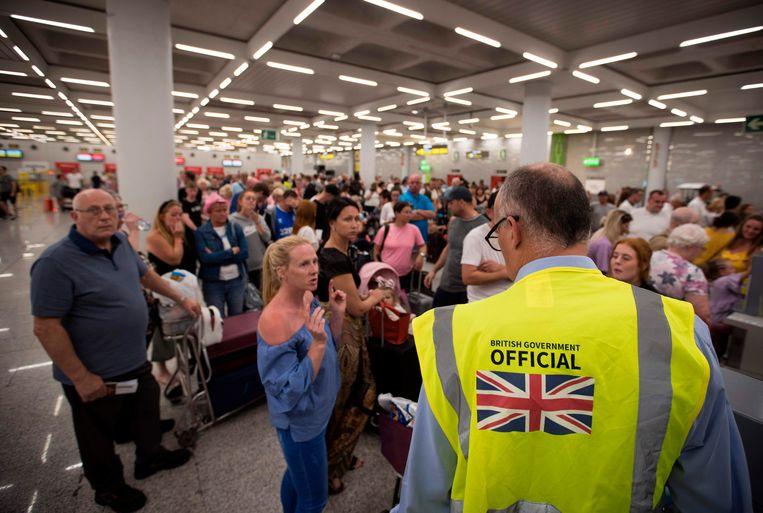 Een Brits ambassademedewerker vangt gestrande reizigers van Thomas Cook op in de Son Sant Joan-luchthaven in Palma de Mallorca. De toeristische sector vreest enorme klappen.  Beeld AFP