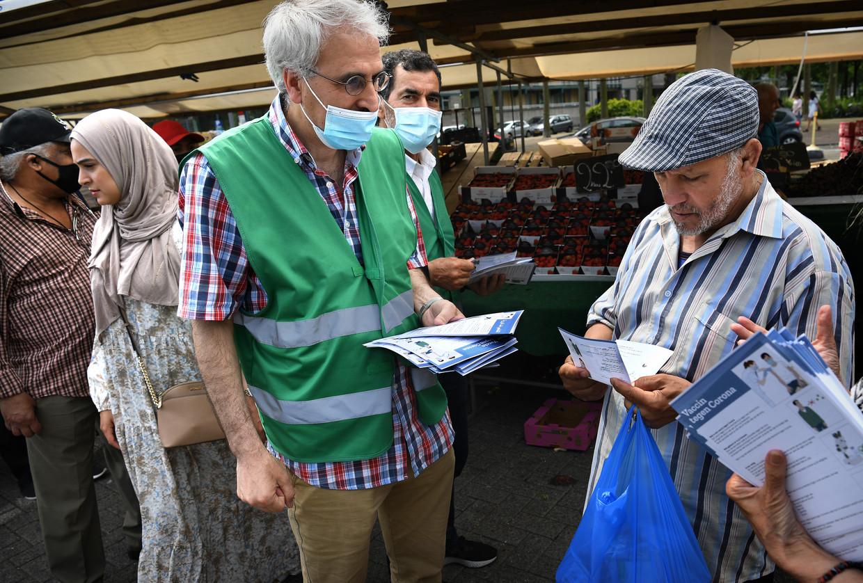 Op de markt in de wijk Delfshaven proberen buurtvrijwilligers mensen aan te sporen zicht te laten vaccineren tegen corona. Beeld Marcel van den Bergh / de Volkskrant