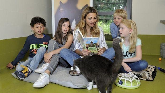 De kat luistert wel naar de actrice maar het bakje eten trekt ook duidelijk de belangstelling van het dier.