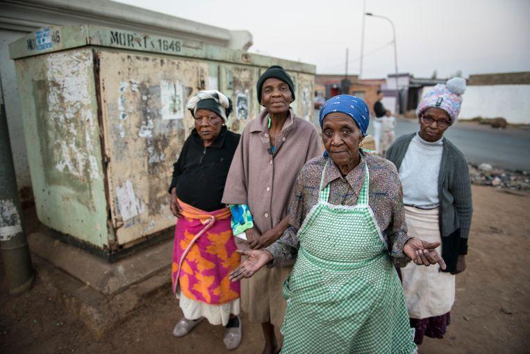 Yvonne Motiki (vooraan) en buurtgenoten staan voor de kapotte transformator. Motiki heeft al langer dan twee maanden geen elektriciteit.  Beeld Bram Lammers