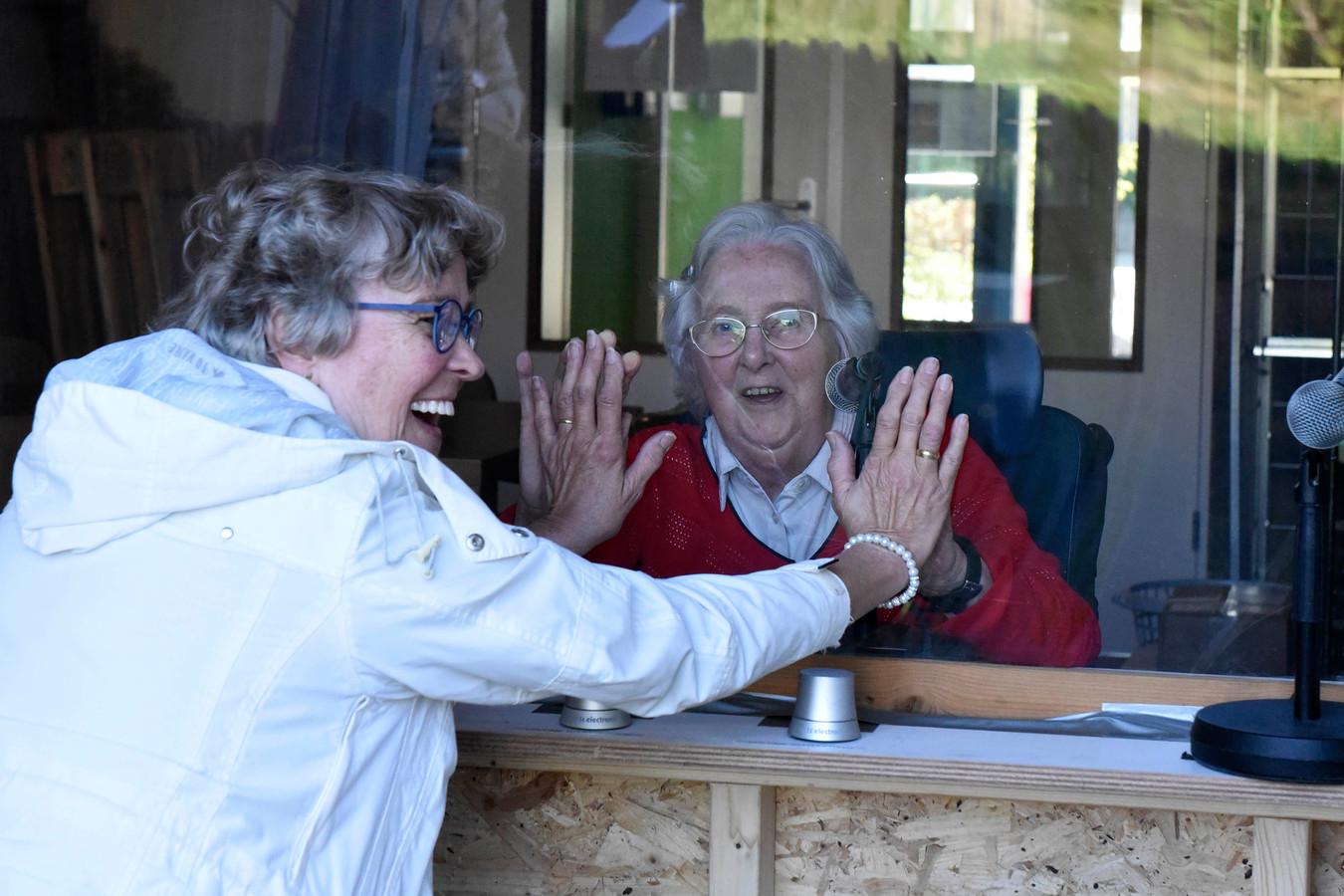 Ada de Kat (68) haar haar zus Corrie Baelde (81) weer zien, maar wel veilig achter het plexiglas.