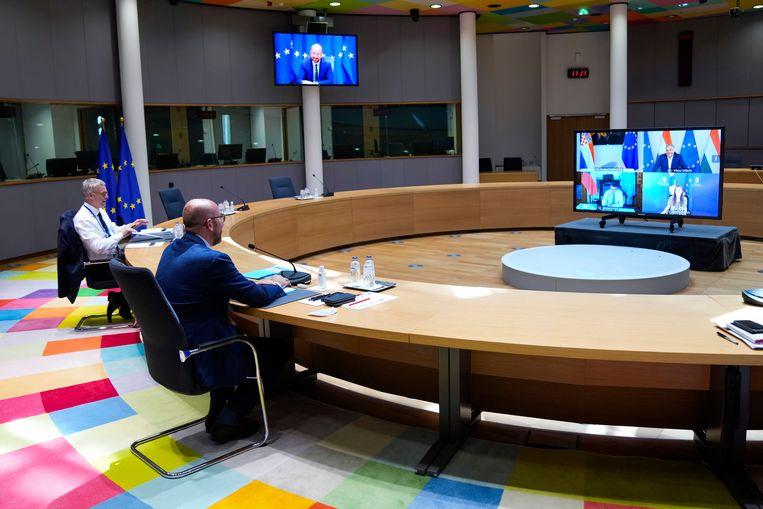 Charles Michel voorzitter van de Europese Raad in een videovergadering met onder andere de Hongaarse premier Viktor Orbán (in het scherm rechtsboven). Beeld AP