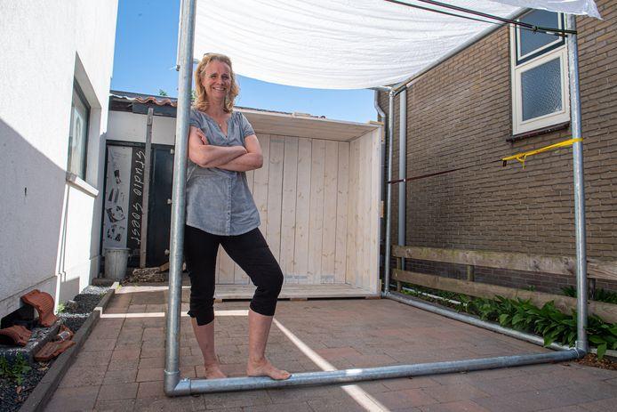 Nadja Willems bij de houten kist waarin ze ondernemers fotografeert.