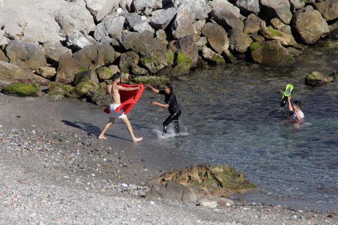 Enkele migranten komen uit de zee in de Spaanse stad Ceuta.