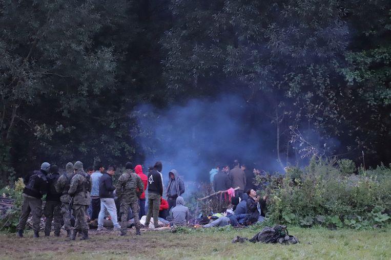 Pools grenswachten controleren een groep vluchtelingen die de grens probeerden oversteken. Beeld Agencja Gazeta via REUTERS