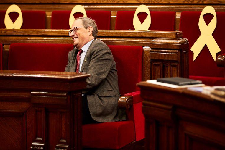 Quim Torra omringd met gele linten ter steun aan de opgepakte politici in het Catalaanse parlement in Barcelona.