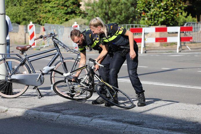 Twee agenten verplaatsten de gebroken wielrenfiets van het slachtoffer.
