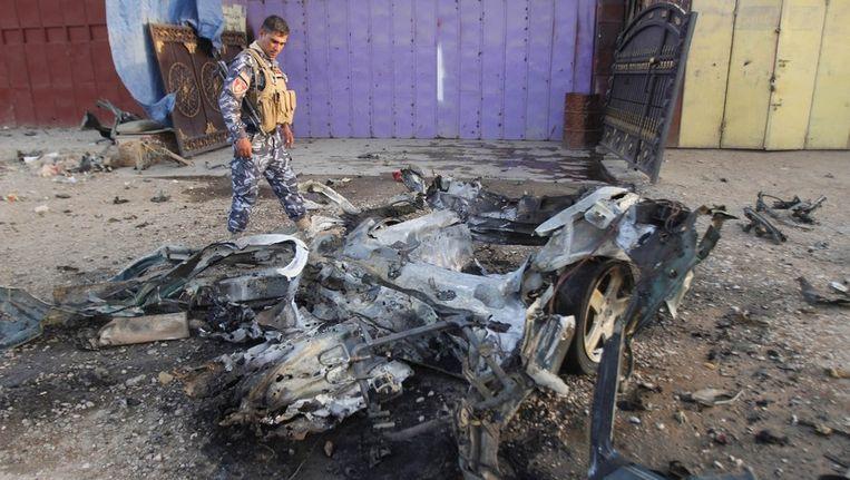 Een Irakese politieman inspecteert de plek van de aanslag. Beeld reuters