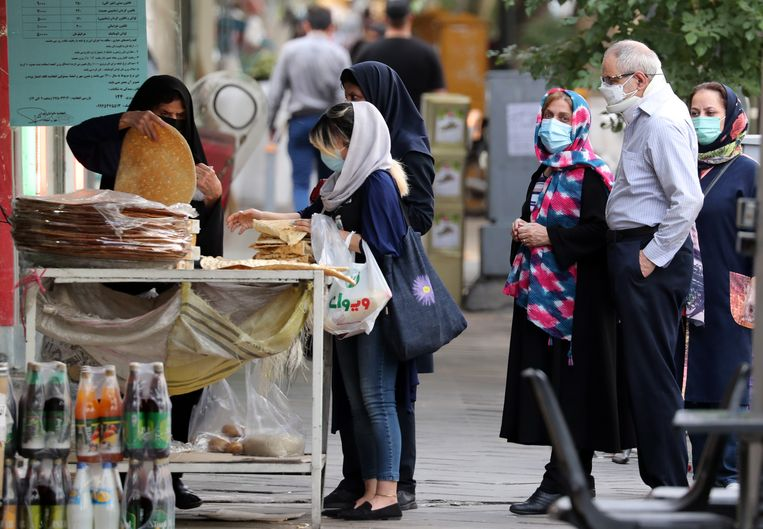 Iraniërs schuiven aan voor brood in Teheran. Beeld EPA