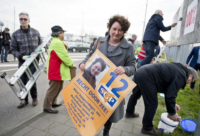 Lilian Janse plakt samen met haar partijleden in Vlissingen affiches voor de gemeenteraadsverkiezingen.