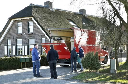 Medewerkers staan bij het bedrijf in het Gelderse Barneveld waar vogelgriep is vastgesteld. Circa 30.000 kippen van het bedrijf worden direct geruimd.