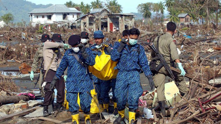 Indonesische hulpverleners brengen een lijk weg, enkele dagen na de verwoestende tsunami van 26 december 2004. Beeld AFP