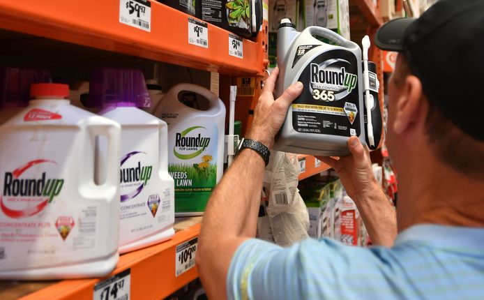 Een man houdt een kan met de pesticide Roundup omhoog in een winkel. Archiefbeeld.