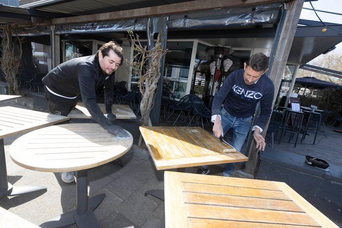 René Peters en Mirzah Durmit van restaurant Lodewijk schuren en schilderen de tafeltjes zodat het er weer top uitziet als volgende week de terrassen weer opengaan.