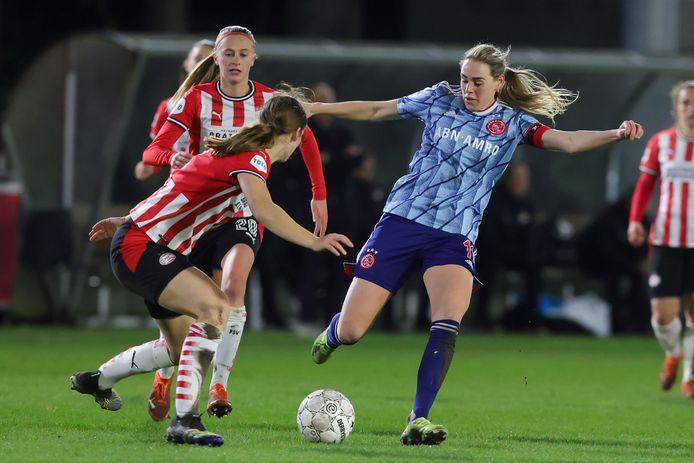 Marjolijn van den Bighelaar van Ajax aan de bal. Zij wordt verdedigd door Aniek Nouwen. Op de achtergrond Julie Biesmans van PSV.