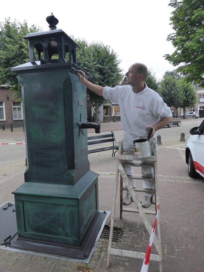 Schilder Wout van Erp zet de Gestelse Pomp weer netjes in de lak.