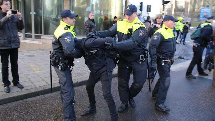 Een van de demonstranten wordt gearresteerd.
