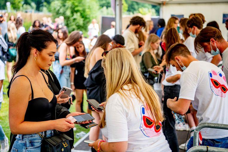 Bezoekers van een festival in Amsterdam tonen bij de entree hun coronatestbewijs. Beeld Robin Utrecht