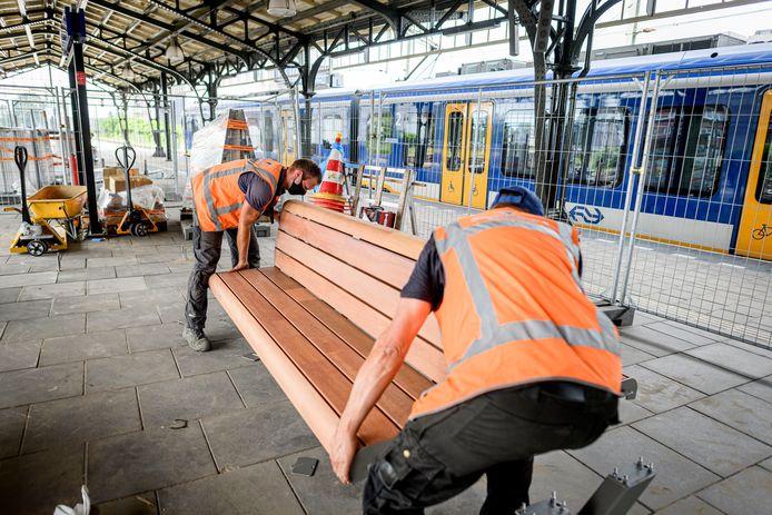 Adriaan Boudestijn (achter) en Jaap Hogedoorn van Streetfurniture plaatsen een nieuwe bank op station Hengelo.