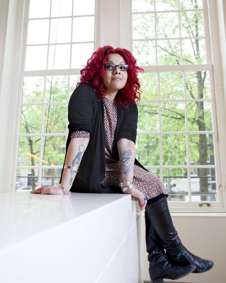 'Mijn rode haar zegt: hier ben ik. Op mijn rechteronderarm heb ik Sekhmet laten tatoeëren - leeuwenkop, vrouwenlichaam - de godin van wraak en seks. Op m'n andere arm staat Mohamed Mamoud, de straat waar ik ben aangerand. Eronder staat Vrijheid.' Beeld Maartje Geels