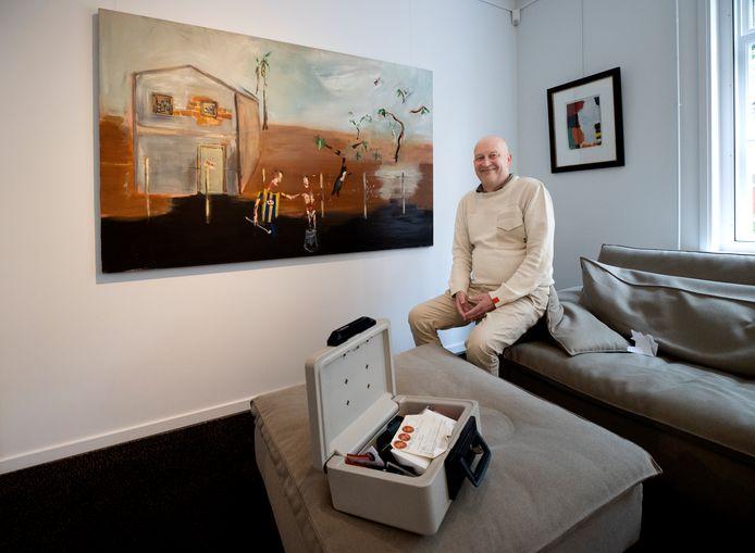 Peter Metzemaekers met zijn geldkistje, voor een schilderij van Jeroen Vrijsen.