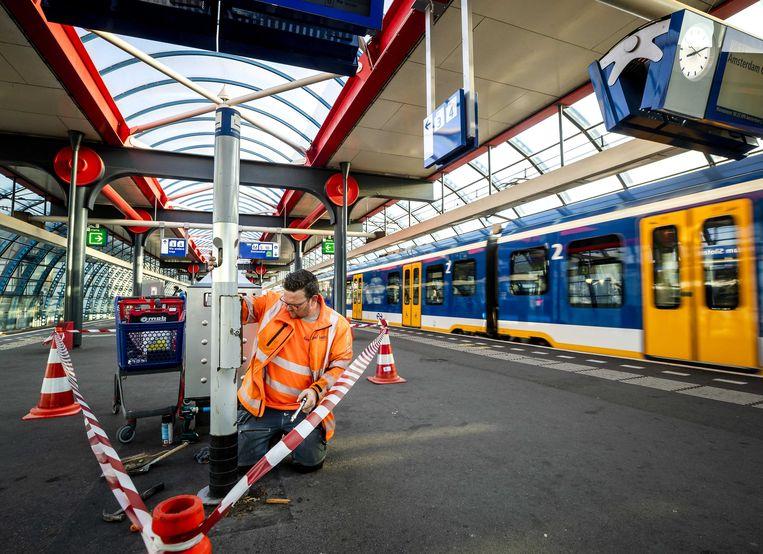Een medewerker van ProRail verwijdert een van de laatste rookpalen van Nederland op station Sloterdijk. De stations worden geheel rookvrij.  Beeld ANP