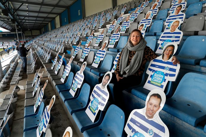 Suze naast haar eigen afbeelding en die van andere mensen die de strijd tegen kanker steunden in stadion De Vijverberg in Doetinchem.